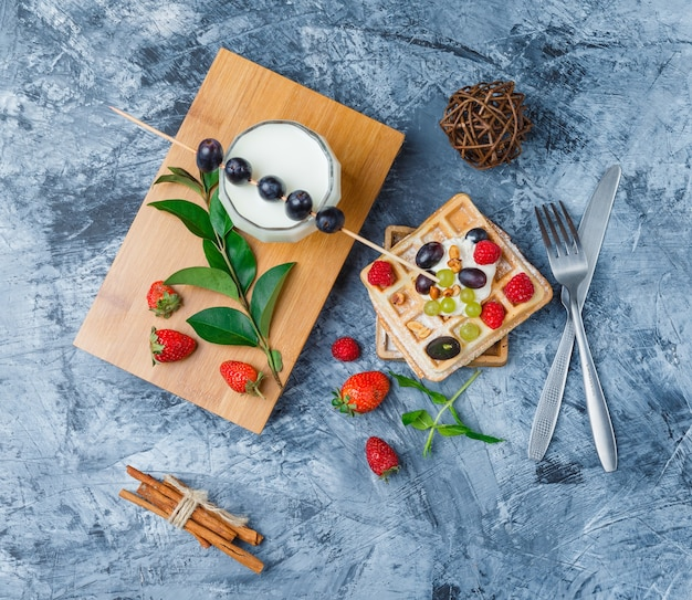 Waffeln und früchte mit milch, pflaumen mit stangen, zimtstangen und erdbeeren Kostenlose Fotos