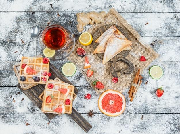 Waffeln und teaon holzbrett mit beeren und zitrusfrüchten Kostenlose Fotos