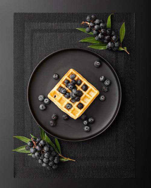 Waffelplatte mit trauben auf einem dunklen stoff Kostenlose Fotos