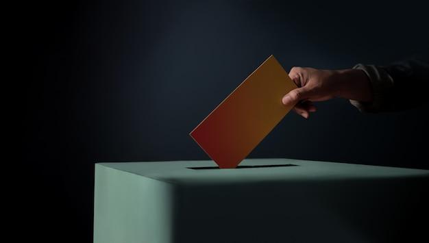 Wahlkonzept. person, die eine wahlkarte in die wahlurne fallen lässt, dunkler filmton Premium Fotos