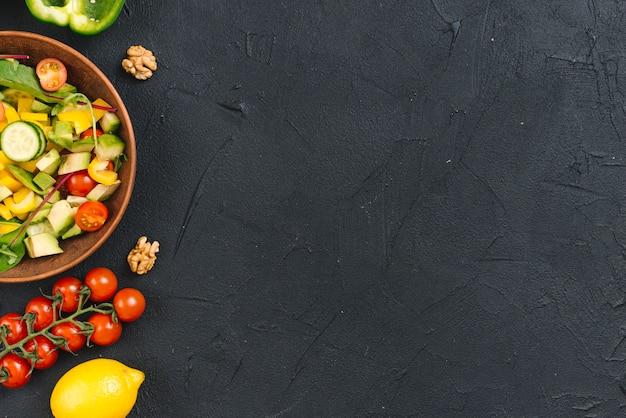 Walnuss- und frischgemüsesalat auf schwarzem konkretem hintergrund Kostenlose Fotos
