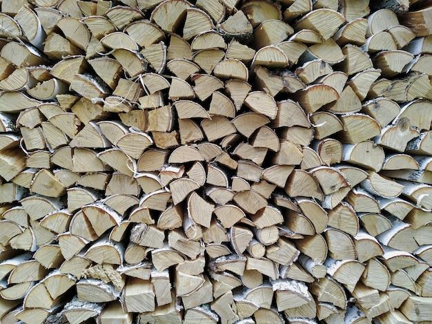 Wand aus gestapeltem brennholz. trockene birke für den ofen. protokolliert hintergrund Premium Fotos