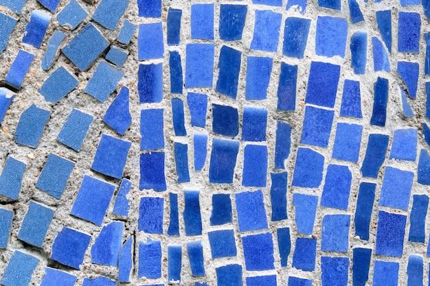 Wand der blauen zerquetschten mosaikfliesen als hintergrund. Premium Fotos