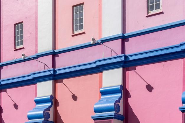 Wand eines gebäudes in den farben blau, rosa und lila unter dem sonnenlicht gemalt Kostenlose Fotos