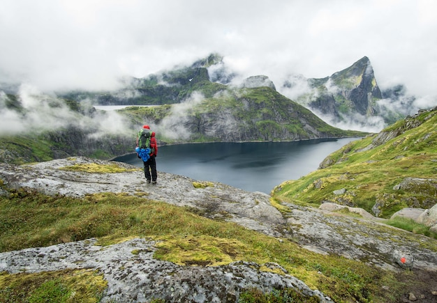 Wanderer, der an einem nebligen tag neben einem see in den lofoten steht Kostenlose Fotos