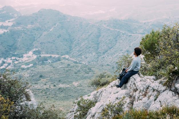 Wanderer, der auf felsen sitzt Kostenlose Fotos