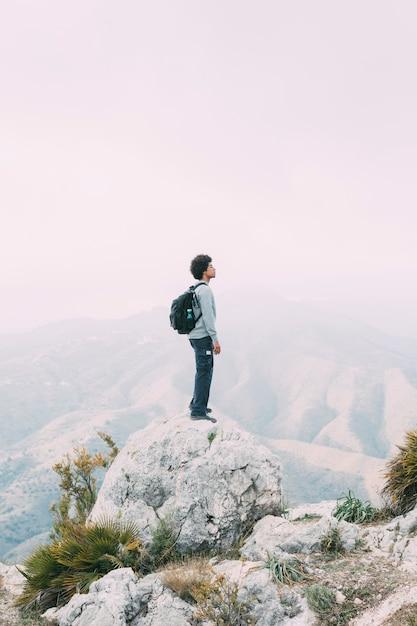 Wanderer, der auf felsen steht Kostenlose Fotos