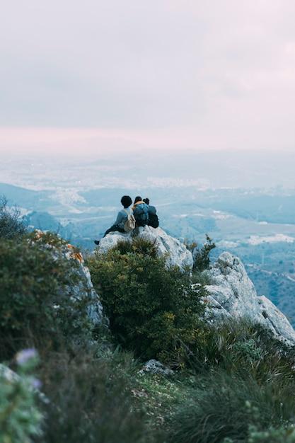 Wanderer sitzen auf einem felsen Kostenlose Fotos
