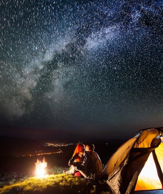 Wanderer sitzen und küssen in der nähe von lagerfeuer und zelt unter sternen Premium Fotos