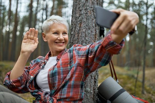 Wandererin in aktivkleidung, die selfie mit smartphone nimmt Kostenlose Fotos