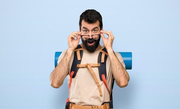 Wanderermann mit gläsern und überrascht über lokalisiertem blauem hintergrund Premium Fotos