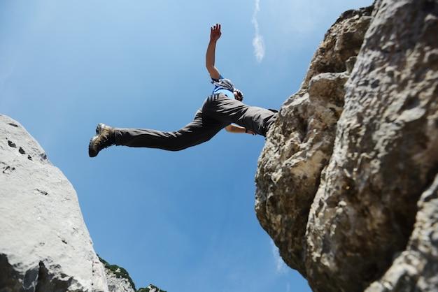 Wandern des mannes, der über die berge zum erfolg springt Premium Fotos