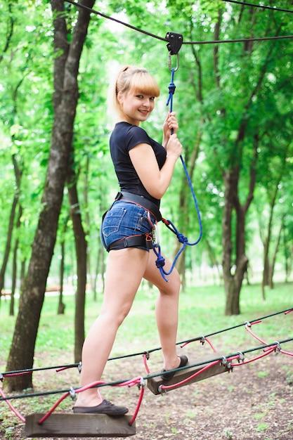 Wandern im schönen sportmädchen des seilparks Premium Fotos