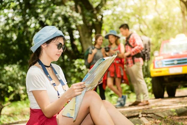 Wandern - wanderer auf der karte. paar oder freunde navigieren zusammen lächelnd glücklich während camping reisen wanderung im freien im wald. junge gemischte rasse asiatische frau und mann. Premium Fotos