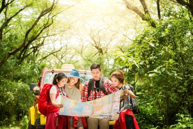 Wandern - wanderer auf der karte. paar oder freunde navigieren zusammen lächelnd glücklich während camping reisen wanderung im freien im wald. junge gemischte rasse asiatische frau und mann. Kostenlose Fotos