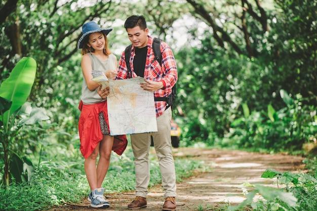 Wandern - wanderer, die karte betrachten. die paare oder freunde, die zusammen glücklich lächelnd während der kampierenden reise wandern, wandern draußen in wald. asiatische frau und mann der jungen mischrasse. Premium Fotos