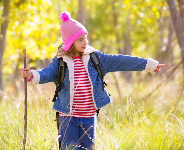 Wanderndes kindermädchen mit rucksack finger im autum wald zeigend Premium Fotos