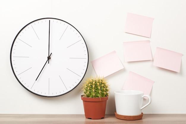 Wanduhr, rosa aufkleber, kaktus und cup auf einem weiß. arbeitsbereich verspotten Premium Fotos