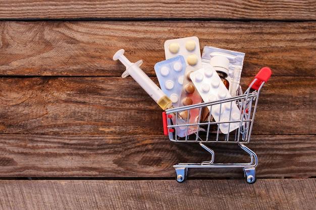 Warenkorb mit pillen, spritze auf dem alten hölzernen hintergrund Premium Fotos