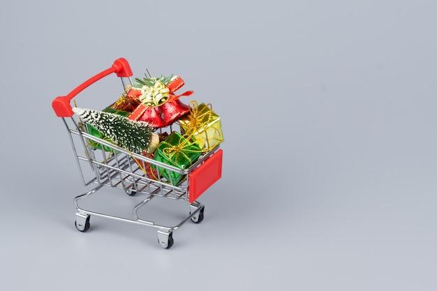 Warenkorb mit weihnachtsbaum- und miniaturgeschenkboxen auf grauem hintergrund Premium Fotos