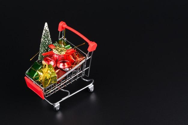 Warenkorb mit weihnachtsbaum und miniaturgeschenkboxen auf schwarzem hintergrund Premium Fotos