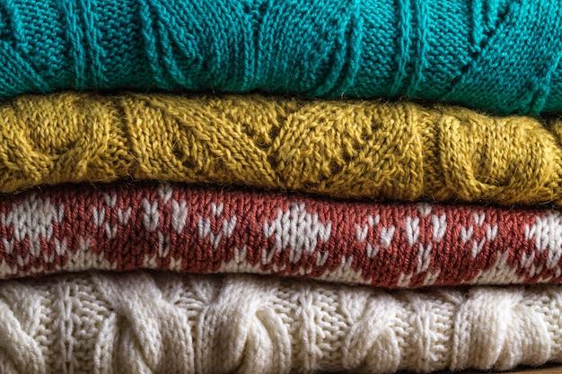 Warme, gestrickte, winterkleidung auf einem hölzernen hintergrund. hässliche weihnachtsstrickjacke Premium Fotos