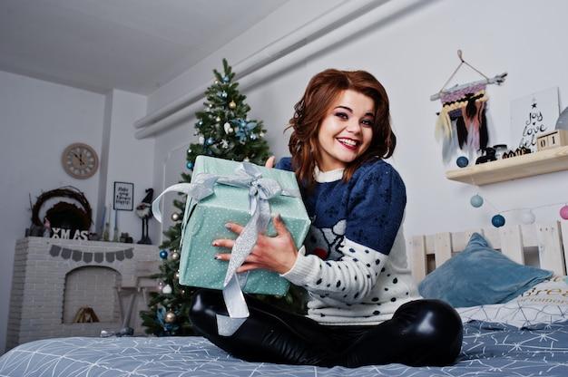 Warme strickjacke der mädchenabnutzung, die auf dem bett gegen baum des neuen jahres mit geschenkkasten an den händen auf studio sitzt. frohe winterferien konzept. Premium Fotos