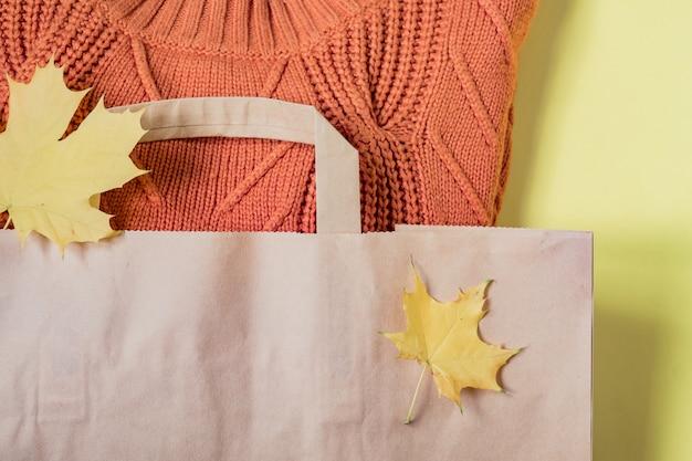 Warme strickjacke der orange frau im papierhandwerkspaket auf gelb Premium Fotos