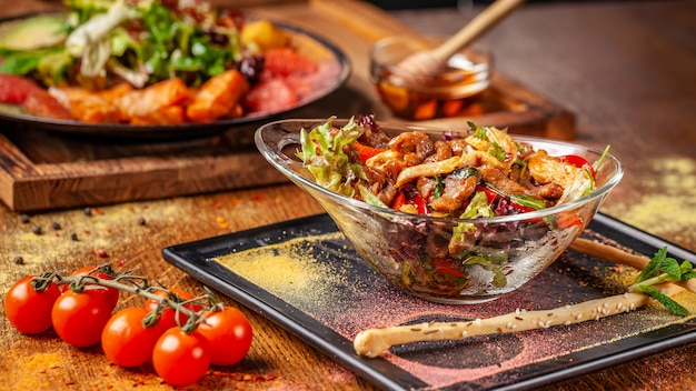 Warmer salat mit rindfleisch und hühnchen, paprika und honig-minz-sauce. Premium Fotos