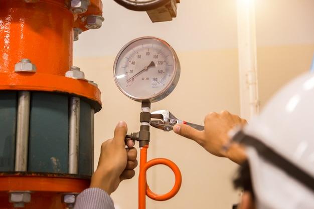 Wartung des asiatischen ingenieurs zur überprüfung der technischen daten der systemausrüstung kondensator wasserpumpe und manometer Premium Fotos