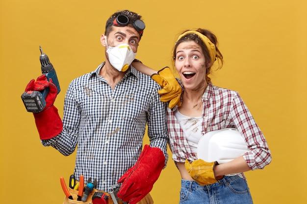 Wartungsarbeiter in freizeitkleidung mit baumaschinen, die überrascht aussahen, trauten ihren augen nicht, dass sie ihre arbeit so schnell beendet hatten. teamwork und plötzlichkeitskonzept Kostenlose Fotos