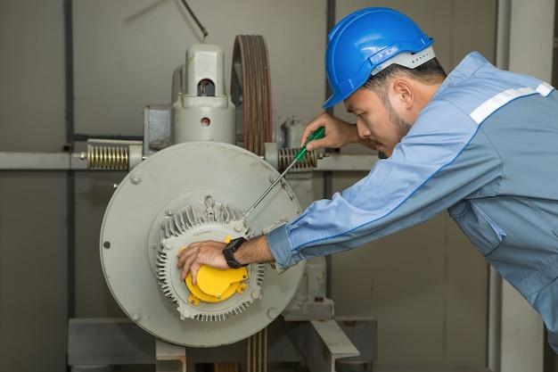 Wartungsingenieur, der aufzug motor für aufzüge repariert Premium Fotos