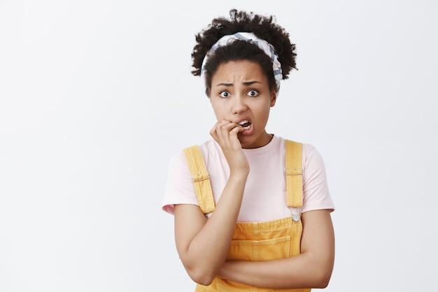 Was ist, wenn jemand weiß, dass ich es bin? porträt einer nervösen schuldbewussten niedlichen frau mit dunkler haut in trendigen gelben overalls und stirnband, beißenden fingernägeln und stirnrunzeln, besorgt und verärgert blickend Kostenlose Fotos