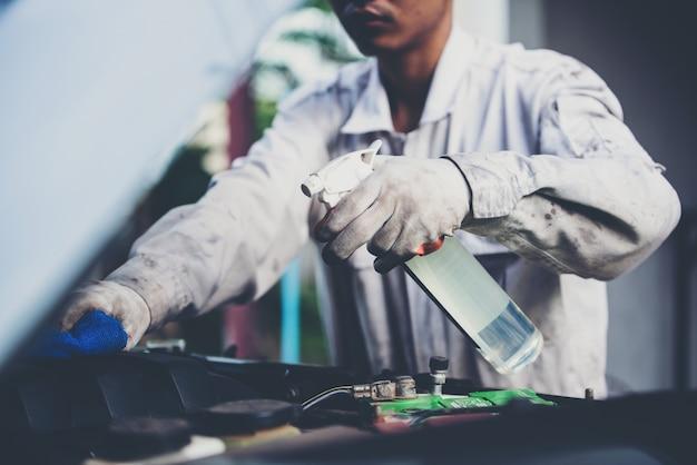 Waschanlagearbeitskraft, die eine weiße uniform steht einen schwamm trägt, um das auto in der waschanlagemitte, konzept für autopflegeindustrie zu säubern. Kostenlose Fotos