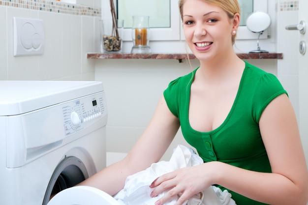 Waschende kleidung der frau mit maschine Premium Fotos