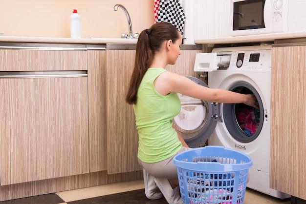 Waschende kleidung der jungen fraufrau nähern sich maschine Premium Fotos