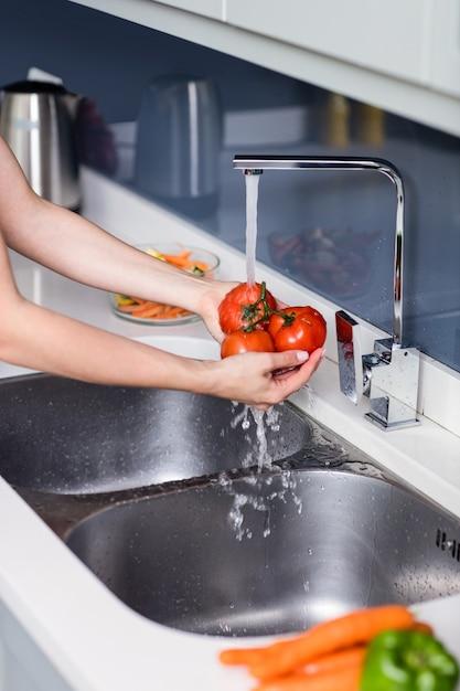 Waschende tomaten der frau am spülbecken Premium Fotos