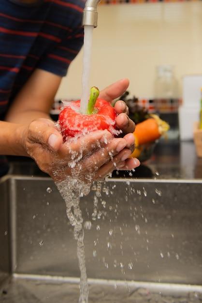 Waschendes gemüse der frau auf dem worktop nahe, zum in einen modernen kücheninnenraum zu sinken Premium Fotos