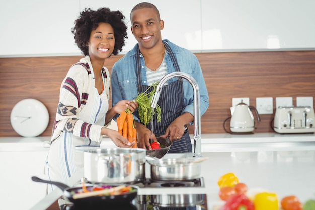 Waschendes gemüse des glücklichen paars in der küche Premium Fotos