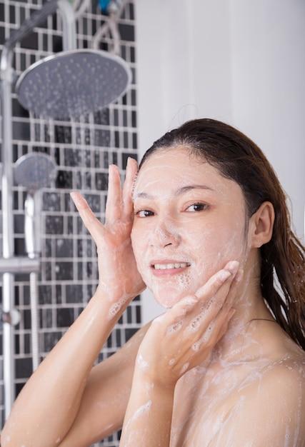 Waschendes gesicht der frau in der schäumenden dusche Premium Fotos