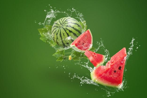 Wasser, das an spritzt geschnitten von der wassermelone auf grünem hintergrund Premium Fotos