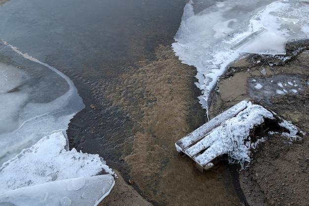 Wasser fließt zwischen eisschollen. die oberfläche eines gefrorenen flusses an einem wintertag. Premium Fotos