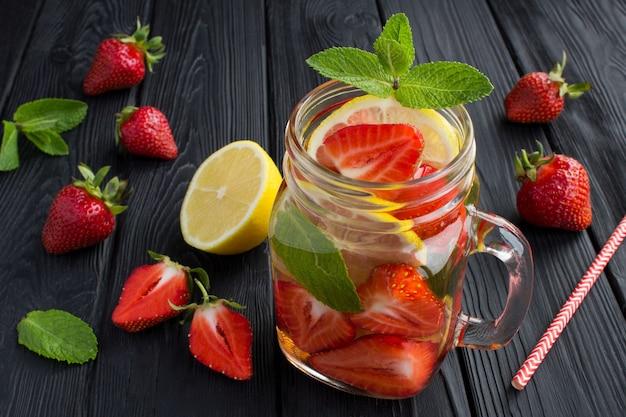 Wasser mit erdbeere und zitrone in das glas auf dem schwarzen tisch gießen Premium Fotos