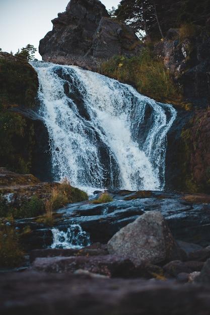 Wasserfälle zwischen waldblick während des tages Kostenlose Fotos