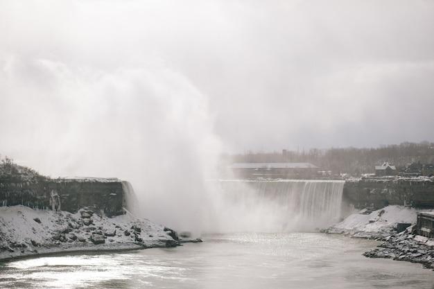 Wasserfall im winter mit bäumen im hintergrund in den niagarafällen in ontario kanada Kostenlose Fotos