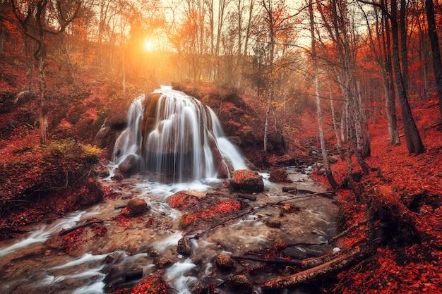 Wasserfall in gebirgsfluss im herbstwald bei sonnenuntergang Premium Fotos