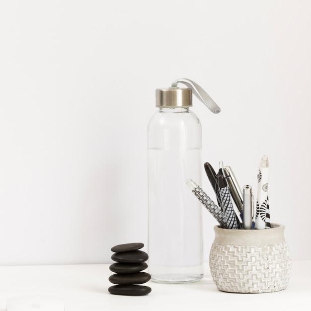 Wasserflasche mit einer auswahl an stiften und massagesteinen Kostenlose Fotos