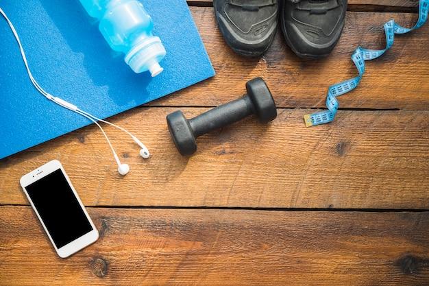 Wasserflasche; sportschuhe; kopfhörer; handy; hanteln und maßband auf hölzernen hintergrund Kostenlose Fotos