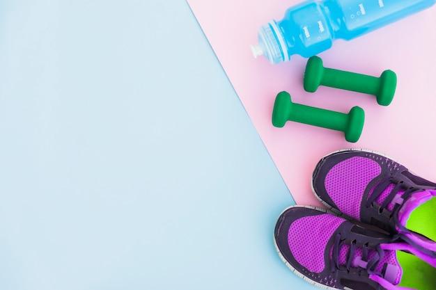 Wasserflasche; sportschuhe und hanteln auf rosa hintergrund