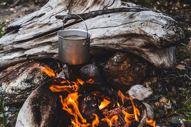 Wasserkocher über feuer hängen Premium Fotos